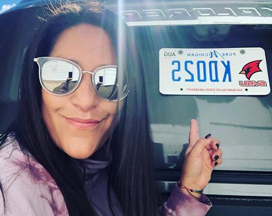 戴着墨镜的女人指着车上的海洋之神app校友车牌